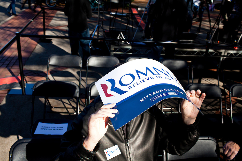 A man shades himself from the sun as he waits for Republican presidential candidate Mitt Romney at a campaign rally on Wednesday, January 18, 2012 in Spartanburg, SC.
