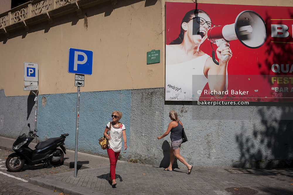 Women pass each other underneath a large advertising billboard featuring a shouting model holding a loudhailer, on a street corner, on 20th July, in Porto, Portugal. There is a message in this ad campaign of volume - to brashly get one's message heard. (Photo by Richard Baker / In Pictures via Getty Images)