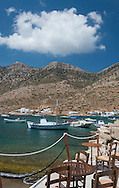 Taverna tables and chairs on a stone pier in the port of Kamares, Sifnos, The Cyclades, Greek Islands, Greece, Europe