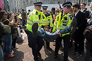 An activist with Extinction Rebellion is arrested during the London protest about climate change in a blocked-off Oxford Circus , on 17th April 2019, in London, England.