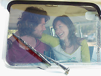 Young couple in van view through window screen