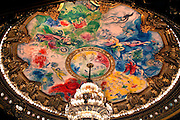 General view of brightly coloured auditorium ceiling, 1964, by Marc Chagall (1887-1985), Palais Garnier, 1860-75, Paris, France. The ceiling, commissioned by Culture Minister Andre Malraux (1901-76), represents scenes from ballets and operas which might be performed at the Opera House. Picture  by Manuel Cohen.