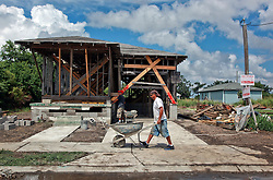 23 August 2013. Lower 9th Ward, New Orleans, Louisiana.<br /> Katrina 8 years later. In a tale of two cities, the hardest hit neighbourhoods struggle to revitalize and return. Contractors working for Brimmer Construction Services begin the extensive process of rebuilding a formerly derelict house. Many half finished or blighted properties and vacant overgrown lots remain dotted throughout the landscape. Residents who have returned complain of limited services, infrequent police patrols, high crime rates, rampant mosquitos and uncontrolled vermin. <br /> Photo; Charlie Varley