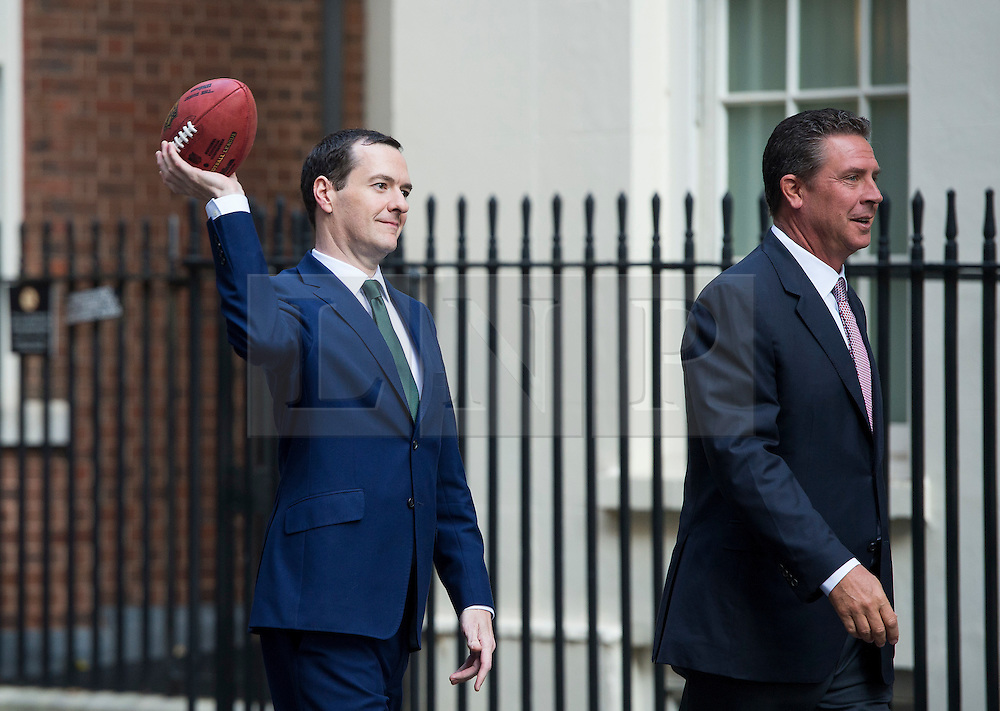 © Licensed to London News Pictures. 02/10/2015. London, UK. British chancellor GEORGE OSBORNE throwing an american football with DAN MARNO (right) and Curtis Martin (not pictured) after meeting with NFL team owners, execs and former stars at Downing Street ahead of this weekend NFL game at Wembley stadium.  Photo credit: Ben Cawthra/LNP