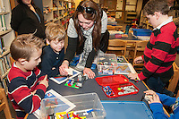 """Angela Stafford demonstrates to Lucca Santos and Mason Sleeper how to attach their flip book card during Elm Street School's """"Let Go Your Mind"""" Lego program after school on Tuesday.  (Karen Bobotas/for the Laconia Daily Sun)"""