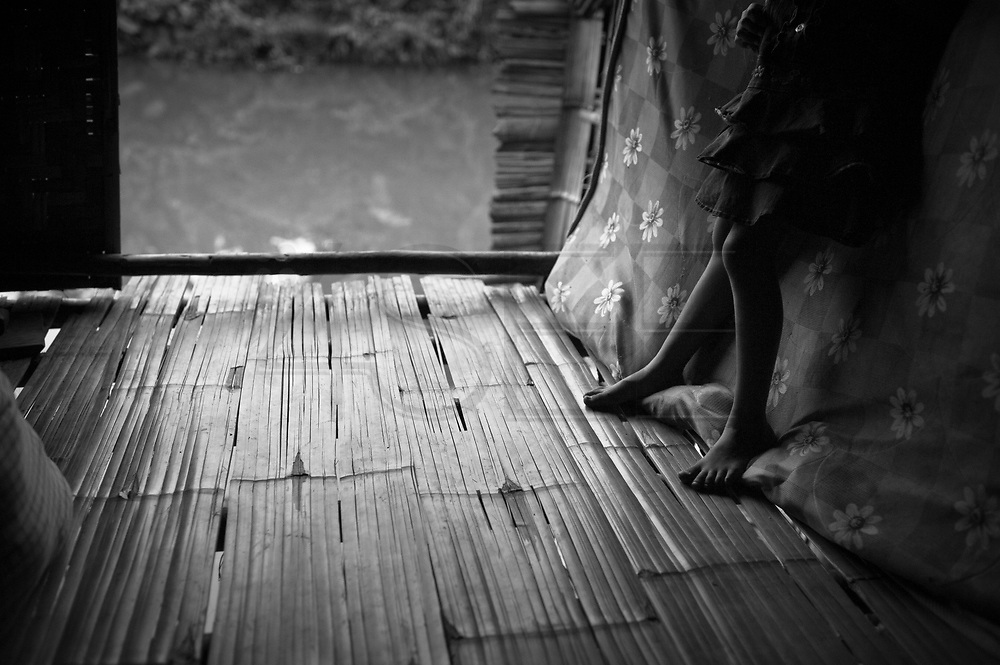 Almost every house in the village has this kind of bamboo floor. This is a normal way to build houses amongst the Lahu people, who in their original way of life would get all their resources from the forest.On the banks of a polluted river, in poorly-built houses, live more than a hundred people from the Lahu tribe. They live in a slum in Chiang Mai, Thailand. The slum has been there for decades.