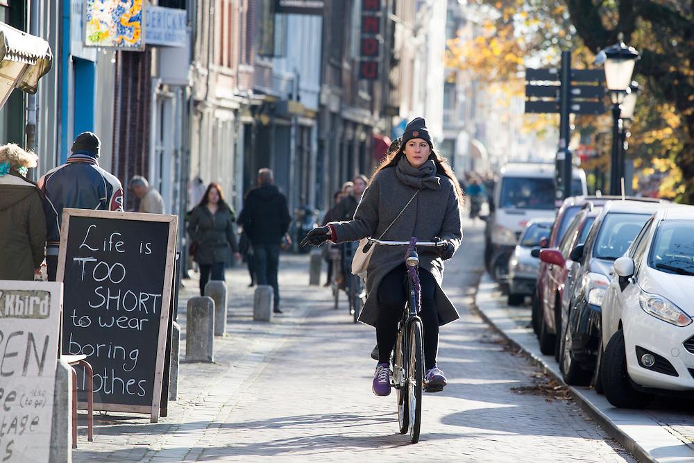 In Utrecht rijden fietsers langs de Oudegracht in de binnenstad. Een vrouw steekt haar hand uit om aan te geven dat ze af wil slaan.<br /> <br /> In Utrecht cyclists ride at the Oudegracht.