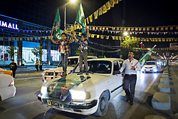 © Licensed to London News Pictures. 27/04/2014. Sulaimaniya, Iraq. Two children holding flags of the Patriotic Union of Kurdistan (PUK) political party stand on the bonnet of a car, driven by a man walking along-side, on the main street of Sulaimaniya, Iraqi-Kurdistan during celebrations in the lead up to the 2014 Iraqi parliamentary elections.<br /> <br /> Although banned in other parts of Iraqi-Kurdistan, the days leading up to an election in Sulaimaniya sees political supporters of all the three main parties parading up and down the main street of the city, waving flags, honking horns, letting off fireworks and firing pistols and rifles into the air.<br /> <br /> The period leading up to the elections, the fourth held since the 2003 coalition forces invasion, has already seen six polling stations in central Iraq hit by suicide bombers causing at least 27 deaths. Photo credit: Matt Cetti-Roberts/LNP