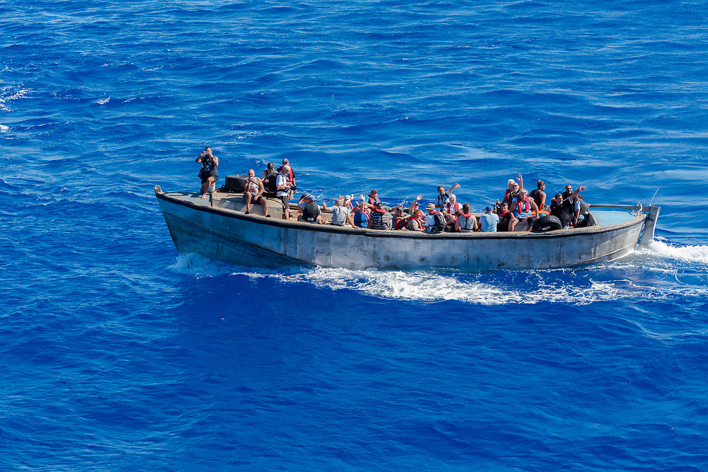 Pitcairn Island, Pacific Ocean-- March 27, 2018.  Natives of Pitcairn island wave to as they set sail to return home after visiting a nearby cruise ship. Editorial Use Only.