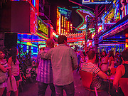 "05 JANUARY 2012 - BANGKOK, THAILAND: Men walk through ""Soi Cowboy,"" a red light district lined with go-go bars and brothels, in Bangkok. Prostitution in Thailand is technically illegal, although in practice it is tolerated and partly regulated. Prostitution is practiced openly throughout the country. The number of prostitutes is difficult to determine, estimates vary widely. Since the Vietnam War, Thailand has gained international notoriety among travelers from many countries as a sex tourism destination. One estimate published in 2003 placed the trade at US$ 4.3 billion per year or about three percent of the Thai economy. It has been suggested that at least 10% of tourist dollars may be spent on the sex trade. According to a 2001 report by the World Health Organisation: ""There are between 150,000 and 200,000 sex workers (in Thailand).""      PHOTO BY JACK KURTZ"