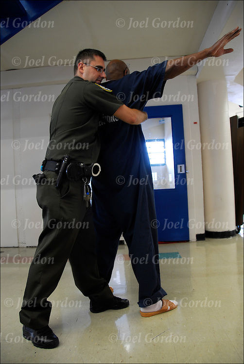 Correction officer in Orange County Jail, frisking and searching inmate before returning to his cell.