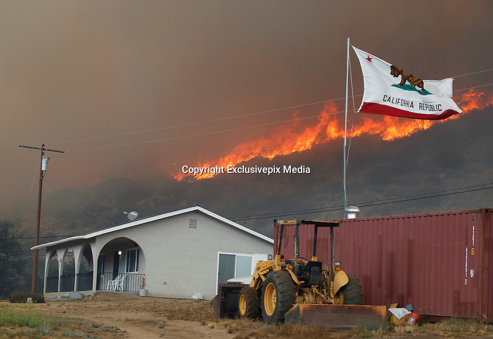 June 20, 2016 - Duarte, California, U.S. - The California state flag flies next to a home on Highway 94 south Potrero on Monday as flames roar behind it. <br /> &copy;Exclusivepix Media