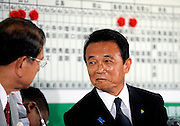 Taro Aso, president of Japan's ruling Liberal Democratic Party and prime minister of Japan, shares a word with party general council chairman Tahashi Sasagawa at his party's headquarters after his party's poor showing in Japan's elections in Tokyo, Japan on Sunday 30 August 2009..