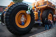 A boy stands in the wheel well of a massive truck used for hauling ore and dirt at an opening day of the Belarus Auto Factory (BelAZ) in Zhodino on Sept. 26, 2009.