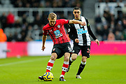 James Ward-Prowse (#16) of Southampton plays the ball backwards under pressure from Miguel Almiron (#24) of Newcastle United during the Premier League match between Newcastle United and Southampton at St. James's Park, Newcastle, England on 8 December 2019.