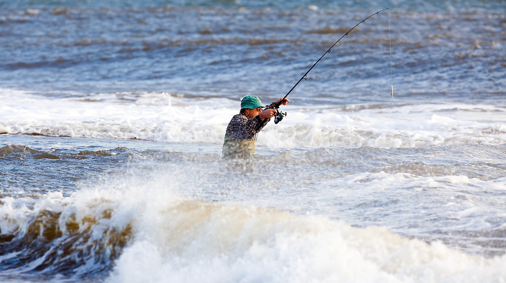 A fisherman working the shoreline at Sandy Hook NJ during durning high surf conditions on a falling tide.   The fall fishing run of striped bass and bluefish is legendary at the park.  Behind the fisherman is the Verranzano-Narrows Bridge linking Staten Island and Brooklyn together.
