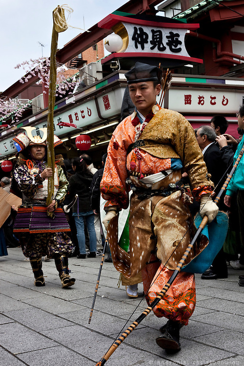 The second archer dressed in Kamakura era clothes, walking through the suvenir area in front of the Senso-ji shrine in Asakusa, on his way to the location by the river where he will take part in Yabusame