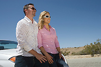 Young couple leaning on car in desert