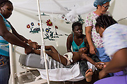 Five-year-old Nicouri Rafael is restrained by her mother, Minerba Ocsena (center), and nurses at Hospital Dr. Alejo Martinez in Ramon Santana. The child struggled for fear of having her blood drawn after receiving a severe burn from a cooking oil accident in Batey Campina, Jan. 11, 2014.