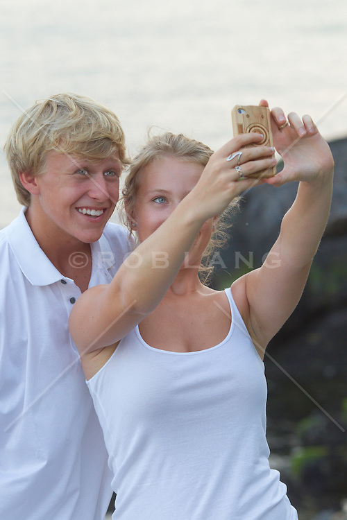 teenagers taking a photograph of themselves with an iphone camera outdoors