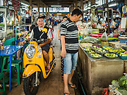 21 JANUARY 2017 - BANGKOK, THAILAND:  A shopper driving a small motorbike in Phra Khanong Market in Bangkok. The market serves a mix of foreign residents, local people, and Burmese migrants.      PHOTO BY JACK KURTZ