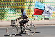 Dar es Salaam, Tanzania - 24.10.15  -  A man with a large Chadema opposition party flag rides his bicycle past poster for ruling party Chama Cha Mapinduzi (CCM) in Dar es Salaam, Tanzania on October 24, 2015.  Tanzania heads to the polls on Sunday, October 25. Photo by Daniel Hayduk