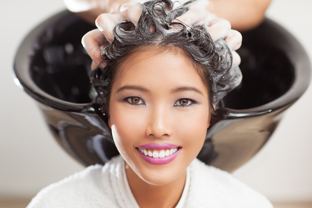 Smiling Asian woman having her hair washed at the hairdresser's.