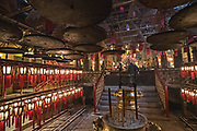 Incense burns inside the Man Mo Temple with giant hanging incense coils is a tribute to the God of Literature and the God of War and was built in 1847 in Sheung Wan District of Hong Kong Island. The Taoist temple is the largest Man Mo Temple in Hong Kong and includes two additional temples for Buddhist and Taoist deities.