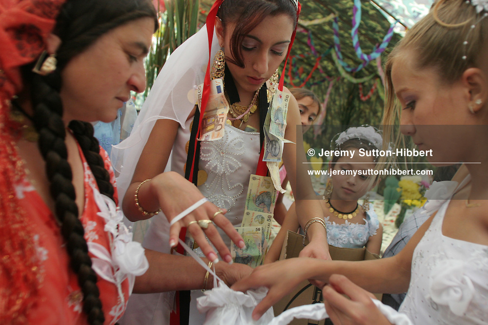 "14 year old roma (gypsy) bride Garoafa Mihai (centre), assisted by friends, organises the ""wedding favours"" to be given as presents, in Sintesti, Romania, on Sunday, Sept. 24th 2006. Day two of the wedding between Garoafa Mihai, aged 14, and Florin 'Ciprian' Lulu, aged 13, Roma (gypsies) from the village of Sintesti,15 kilometres from Bucharest, Romania. Their partnership was decided by their parents and not through love, and under Romanian law is illegal. The children will neither complete legal paperwork for the wedding, nor visit the local Romanian Orthodox church for a blessing. On her wedding day Garoafa wore approximately 30-40,000 USD of gold Franz Josef coins on her dress, part of the large dowry that she takes with her as she begins her married life. For the guests and for the people of the village another 30,000 USD of pigs, approximately 100,  were killed to be eaten and given away as presents of food. Another 30,000 USD was spent on famous Roma musicians to come and sing 'manele'  type music at the wedding extolling the wealth and status of their patrons for the weekend in their songs."