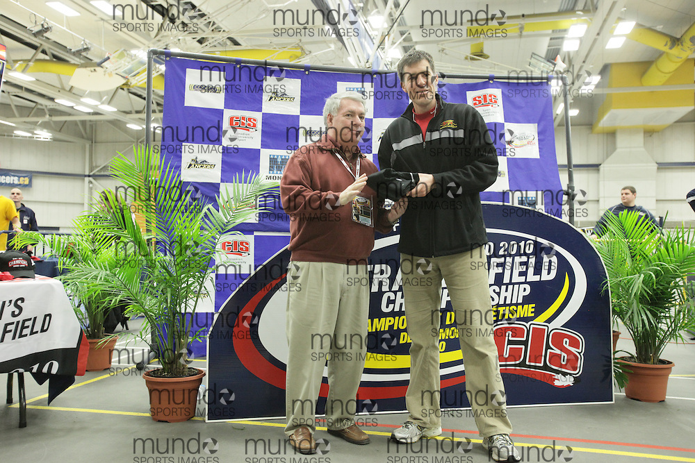 (Windsor, Ontario---13 March 2010) Guelph's Dave Scott Thomas, right, accepts the men's CIS Coach of the year award at the 2010 Canadian Interuniversity Sport Track and Field Championships at the St. Denis Center. Photograph copyright Geoff Robins/Mundo Sport Images. www.mundosportimages.com