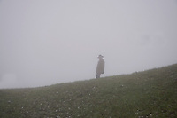 Mt. Rigi, Central Switzerland. Man walking along the brow of a hill in the fog.