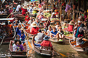 "10 JULY 2011 - DAMNOEN SADUAK, RATCHABURI, THAILAND:  Tourists in boats visit the ""floating market"" in Damnoen Saduak, Thailand, about two hours south of Bangkok. The Thai countryside south of Bangkok is crisscrossed with canals, some large enough to accommodate small commercial boats and small barges, some barely large enough for a small canoe. People who live near the canals use them for everything from domestic water to transportation and fishing. Some, like the canals in Amphawa and nearby Damnoensaduak (also spelled Damnoen Saduak) in Rajburi  province (also spelled Ratchaburi) are also relatively famous for their ""floating markets"" where vendors set up their canoes and boats as floating shops.     PHOTO BY JACK KURTZ"