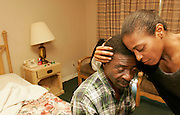 HOUSTON - SEPTEMBER 5: Harold Brown, Jr. is consoled by his companion, April Bowie, as he sits on his bed at the Western Inn in Houston, Monday, Sept. 5, 2005. The pair escaped their 9th Ward home in New Orleans on a tractor tire and made their way to Houston several days later.<br />