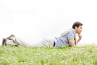 Full length of thoughtful young man lying on grass against clear sky