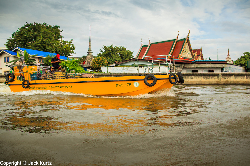"""17 NOVEMBER 2012 - BANGKOK, THAILAND:  A garbage hauling boat enters the Chao Phraya River from a canal in the Thonburi section of Bangkok. Bangkok used to be known as the """"Venice of the East"""" because of the number of waterways the criss crossed the city. Now most of the waterways have been filled in but boats and ships still play an important role in daily life in Bangkok. Thousands of people commute to work daily on the Chao Phraya Express Boats and fast boats that ply Khlong Saen Saeb or use boats to get around on the canals on the Thonburi side of the river. Boats are used to haul commodities through the city to deep water ports for export.    PHOTO BY JACK KURTZ"""