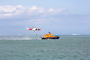 A crew member from HM Coastguard rescue helicopter (G-C1JW)  attempts to land onto the back of the Royal National Lifeboat Institution RNLI Dover Life boat (17-09) during a training exercise in the sea just outside Folkestone Harbour, Folkestone, Kent. UK.(photo by Andrew Aitchison / In pictures via Getty Images)