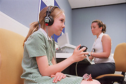 Young girl wearing headphones taking pure tone audiometry test in aural care centre,