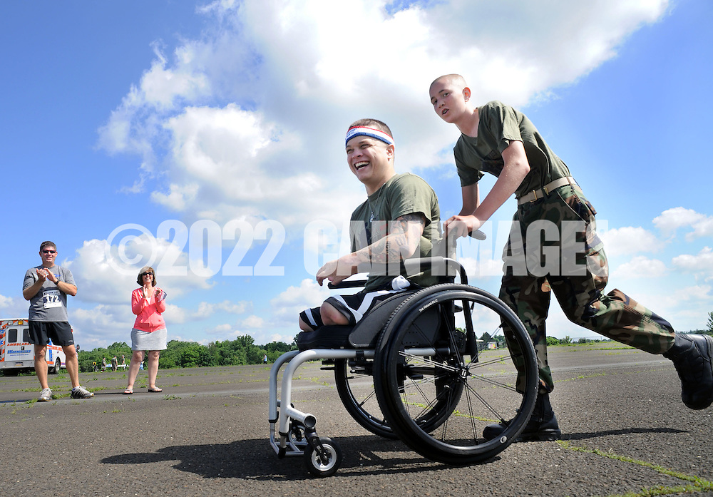 WARMINSTER, PA - JUNE 14: Marine Corporal Tyler Southern is wheeled to the finish line by Lee Sliwinski during the Wounded Hero 5K to support the Honor & Courage Program of Operation Ward 57 June 14, 2014 at Warminster Community Park in Warminster, Pennsylvania. Southern was on his second deployment when he lost both of his legs above the knees, his right arm above the elbow, and shattered his left arm and hand after stepping on an IED in Musa Qala in the Now Zad District of Afghanistan on May 5, 2010. (Photo by William Thomas Cain/Cain Images)