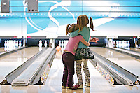 Bailey Burke, 3, holds onto her sister Madison, 5, as they patiently wait for their bowling ball to slowly make its way down the lane Thursday as it skids off the bumper at Sunset Bowling in Coeur d'Alene. The girls made their first bowling trip with their mom as part of a food drive for the Idaho Connections Academy.