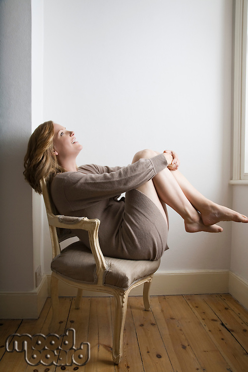 Semi dress woman relaxing on old fashioned chair