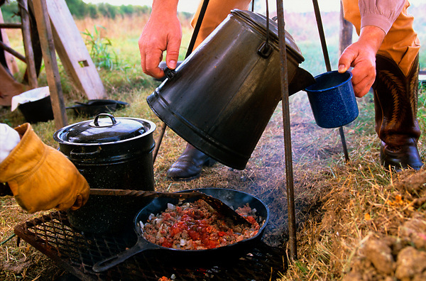close up of two people cooking at a campsite