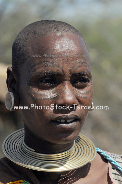 Africa, Tanzania, members of the Datoga tribe Woman in traditional dress, beads and earrings. Beauty scarring can be seen around the eyes,