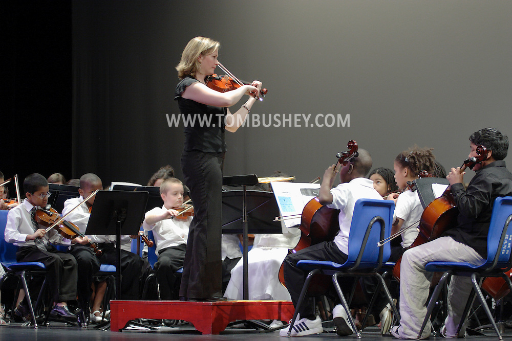 Middletown, NY - A music teacher leads elementary school students during a band concert on the stage at Middletown High School on May 28, 2008.