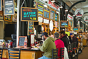 Diners at cafe bar in French Market food market, Decatur Street, French Quarter, New Orleans, USA. Gator on a stick a specialty
