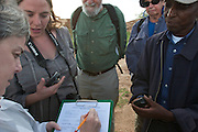Dr. Alexander Njue shows new Earthwatch volunteers how to fill out the water sample field data sheet.
