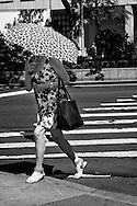 Crosswalk fashion with pattern-coordinated umbrella and  dress; Seen at Lincoln Center, New York City