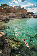 Formentera, Spain, October 2017. Calo des Mort is Compact, simple beach backed by rocky cliffs, with clear waters, fine sand & panoramic views. Formentera is the smallest of Spain's Balearic islands in the Mediterranean Sea. It's reachable by ferry from its more crowded, better known island neighbor, Ibiza, and makes for a popular day-trip destination in the summertime. It's known for its clear waters and long stretches of beach backed by dunes and pine trees. Pastimes include snorkeling and sailing, with equipment rentals and boat charters available. Photo by Frits Meyst / MeystPhoto.com