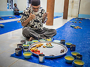 26 JULY 2013 - BANGKOK, THAILAND:   A man prays before eating the Iftar meal at Haroon Mosque in Bangkok. Iftar is the Muslim meal that breaks the day long fast during Ramadan. Ramadan is the ninth month of the Islamic calendar, and the month in which Muslims believe the Quran was revealed. The month is spent by Muslims fasting during the daylight hours from dawn to sunset. Fasting during the month of Ramadan is one of the Five Pillars of Islam. Muslims believe that the Quran was sent down during this month, thus being prepared for gradual revelation by Jibraeel (Gabriel) to the prophet Muhammad.        <br />       PHOTO BY JACK KURTZ