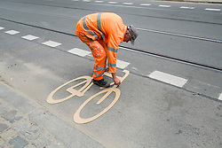 Worker painting sign for new cycle lane on street in bohemian Prenzlauer Berg district of Berlin Germany
