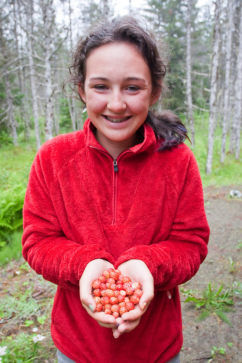 A smiling teenage girl holds two handfuls of wild strawberries in front of her red sweater. MR MRA